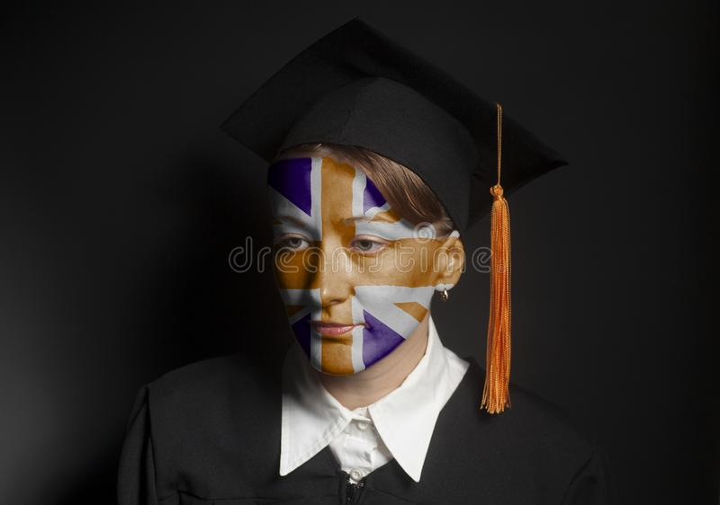 Portrait of Female British bachelor with painted British flag in Black mantle and Graduation Cap. On a black background stock photos