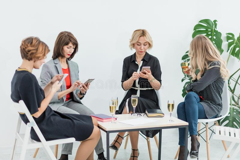 Portrait of female business team in modern studio with glasses of champagne. stock photography
