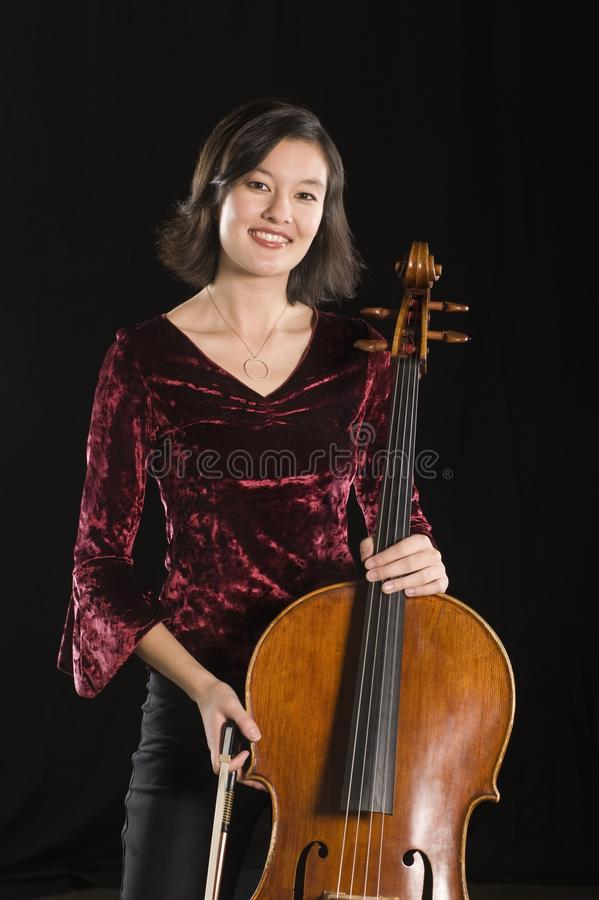 Portrait Of Female Cellist Standing With Cello. Portrait of a beautiful woman standing with cello isolated over black background royalty free stock images