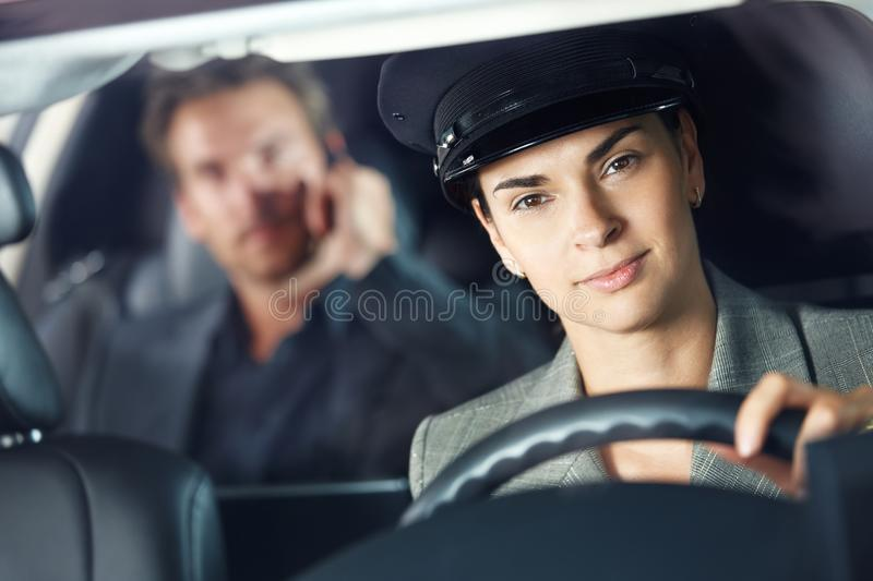 Portrait of female chauffeur. In luxury car stock photography