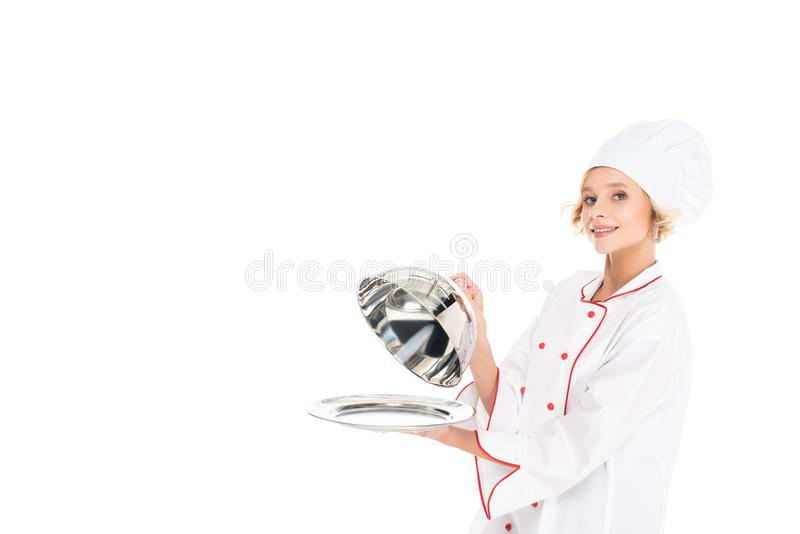 Portrait of female chef with empty serving tray looking at camera. Isolated on white stock photography