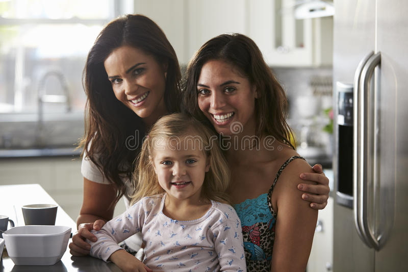 Portrait of female couple in the kitchen with their daughter stock photography