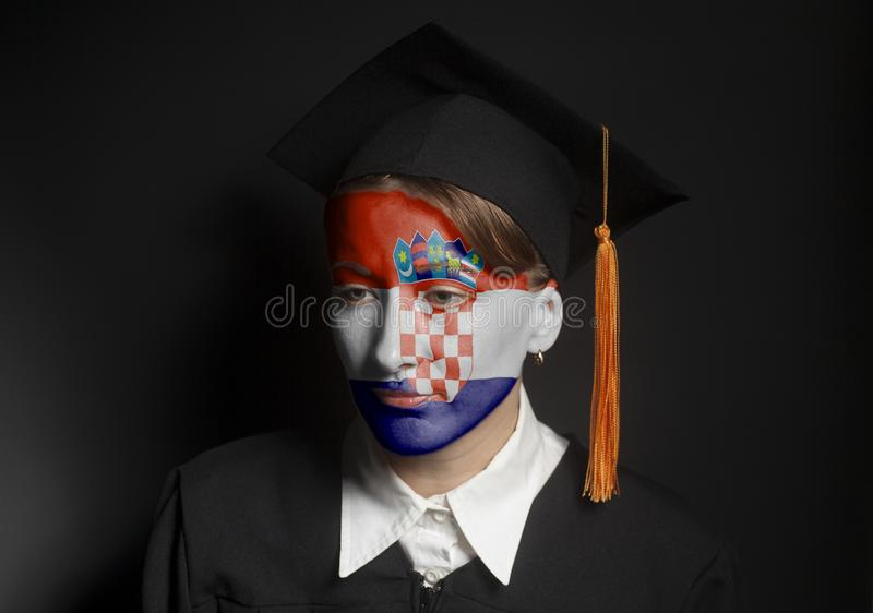 Portrait of Female croatia bachelor with painted Croatia flag in Black mantle and Graduation Cap. On black royalty free stock photo