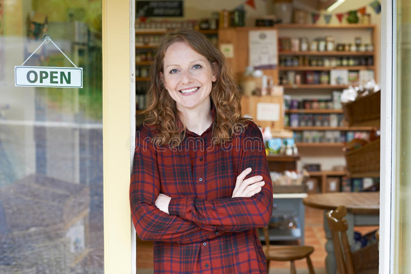 Portrait Of Female Delicatessen Owner Outside Store. Portrait Of Female Delicatessen Owner In Entrance To Store stock photo