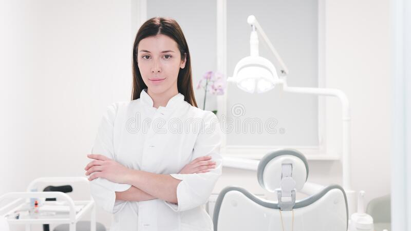 Portrait of female dentist doctor in white uniform at workplace, close-up royalty free stock photography