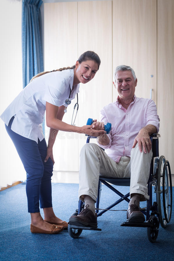 Portrait of female doctor assisting senior man in lifting dumbbell royalty free stock photos