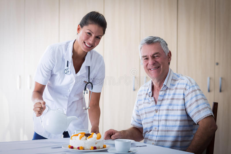 Portrait of female doctor celebration seniors man birthday in living room stock image