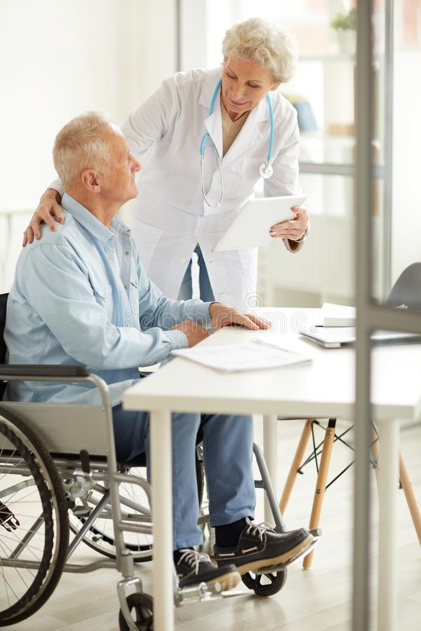 Female Doctor Consulting Elderly Man. Portrait of female doctor consulting handicapped elderly man, copy space stock photo