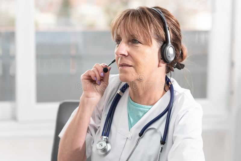 Portrait of female doctor during online medical consultation. Portrait of mature female doctor during online medical consultation royalty free stock photography