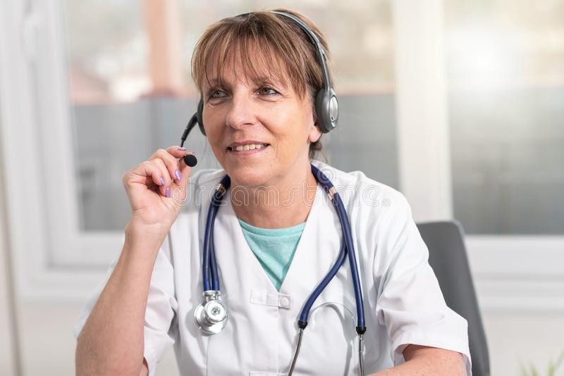 Portrait of female doctor during online medical consultation. Portrait of mature female doctor during online medical consultation stock photo