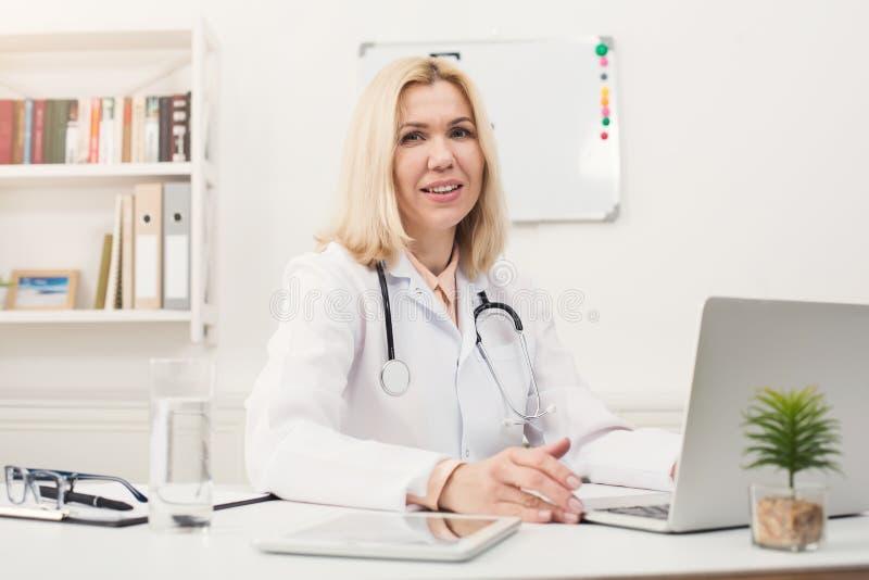 Portrait of female doctor sitting at desktop stock image