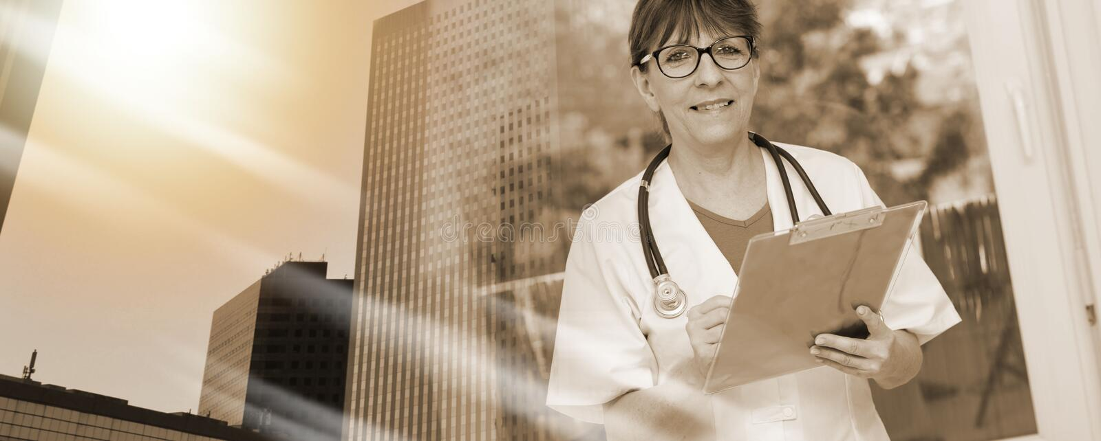 Portrait of female doctor holding a clipboard; multiple exposure stock photography