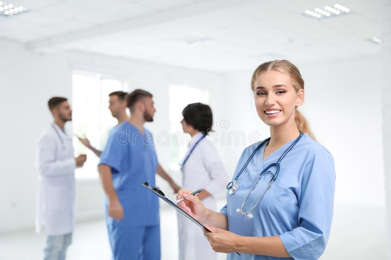 Portrait of female doctor in uniform and her colleagues stock image