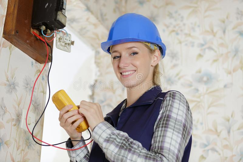 Portrait female electrician using multimeter stock photos
