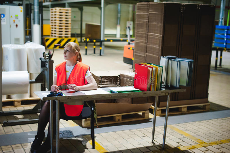 Portrait of a female employee in an orange robe vest in the working space of a production facility, supervises and controls the li stock photo