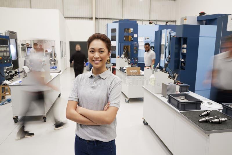 Portrait Of Female Engineer On Factory Floor Of Busy Workshop stock image