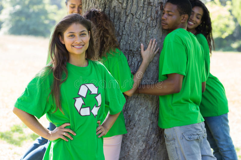 Portrait of female environmentalist. At park with friends hugging tree in background royalty free stock photography