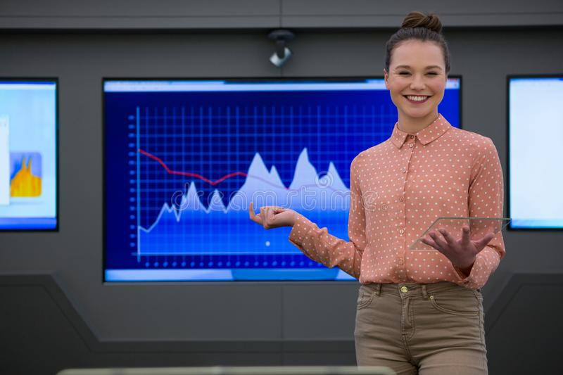 Portrait of female executive giving presentation on graph. In futuristic office stock photography