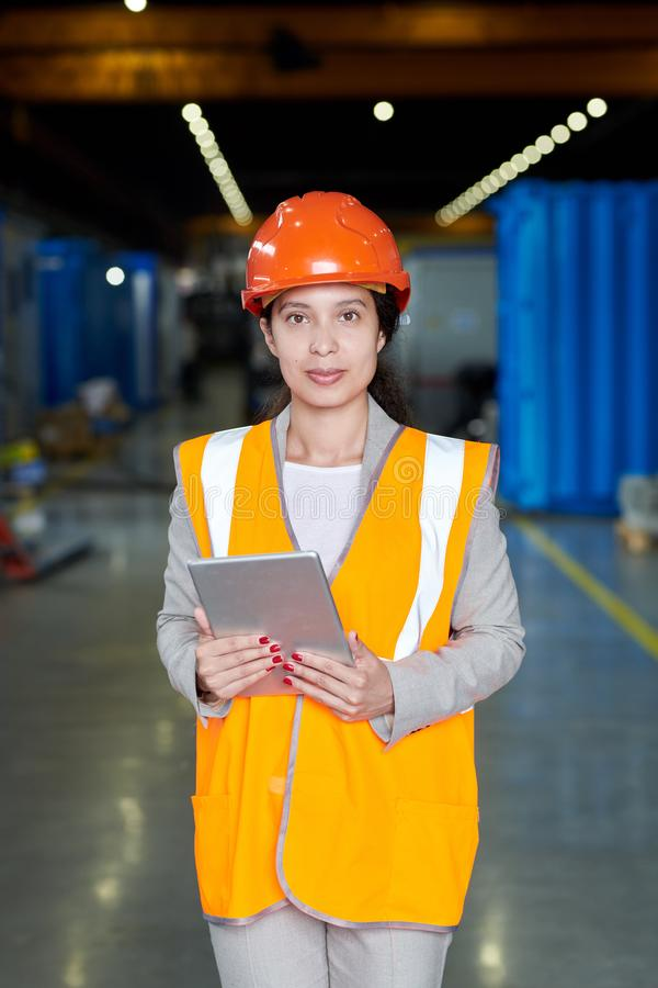 Female Factory Foreman. Portrait of female factory worker wearing hardhat and reflective vest looking at camera and smiling cheerfully while posing in workshop royalty free stock photos