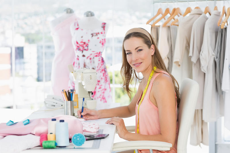 Portrait of a female fashion designer working on her designs. Side view portrait of a young female fashion designer working on her designs in the studio stock photos