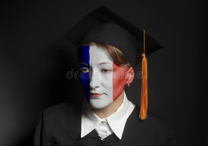 Portrait of Female french bachelor with painted France flag in Black mantle and Graduation Cap. On a black background stock image