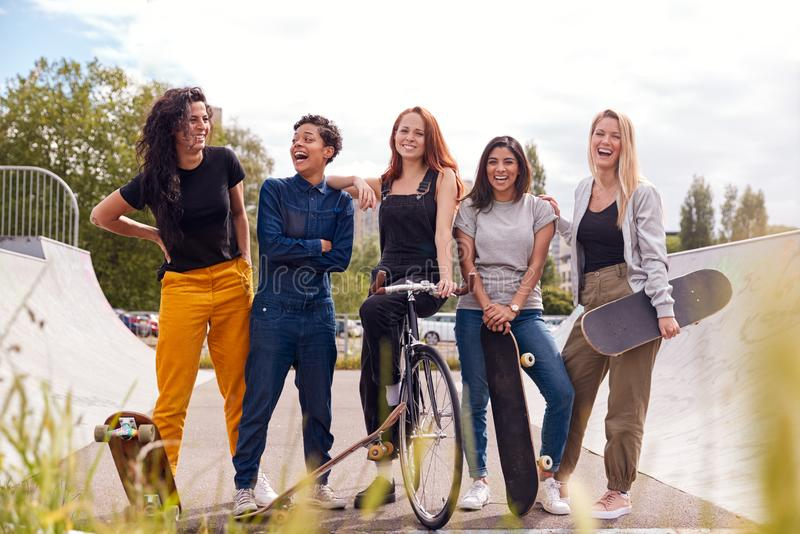 Portrait Of Female Friends With Skateboards And Bike In Urban Skate Park stock image