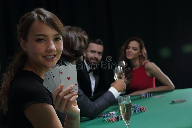 Portrait of the female gambler at the poker table with cards royalty free stock images