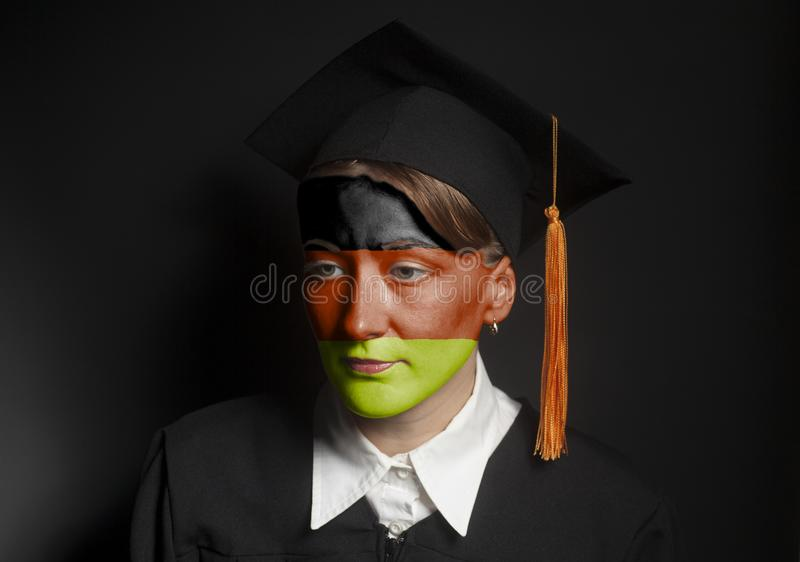 Portrait of Female Germany bachelor with painted German flag in Black mantle and Graduation Cap. On a black background royalty free stock images