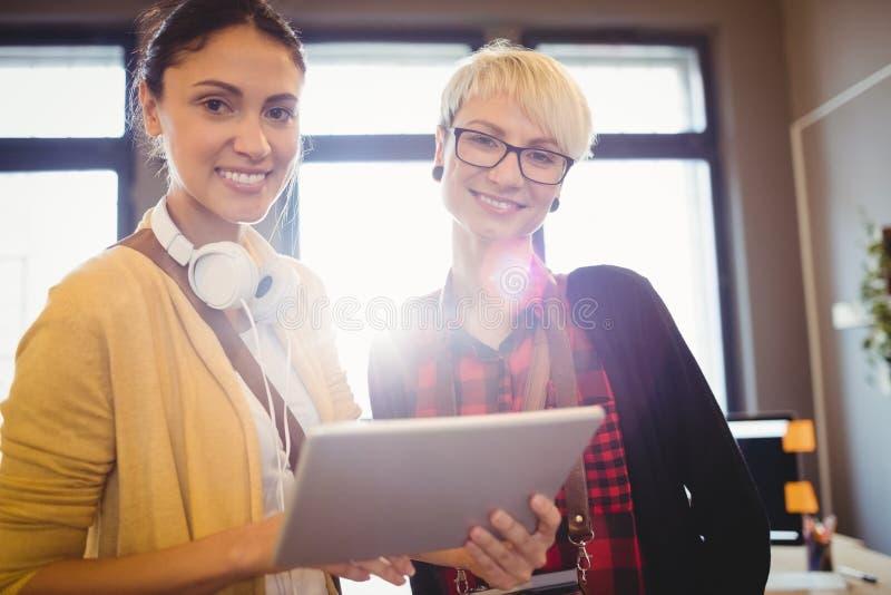 Portrait of female graphic designer using digital tablet. Portrait of smiling female graphic designer using digital tablet in office stock images