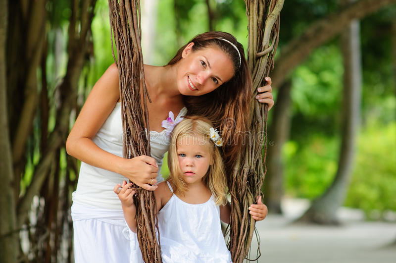 Portrait female and her daughter in tropical park stock image