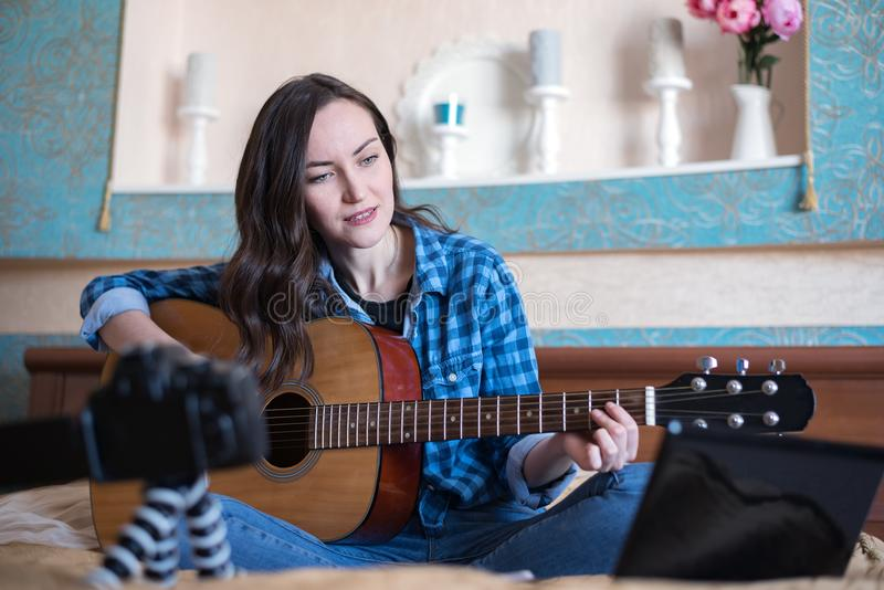 Portrait of female hipster blogger with an acoustic guitar writes a personal blog on your SLR camera.  stock image