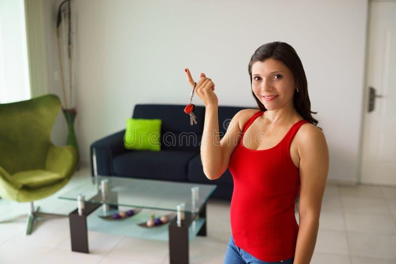 Portrait female home owner smiling holding keys new house stock images