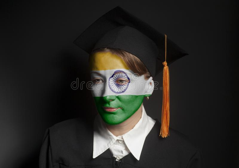Portrait of Female Indian bachelor with painted Indian flag in Black mantle and Graduation Cap. On a black background royalty free stock photography