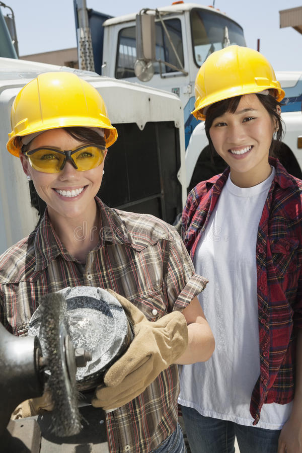 Portrait of female industrial worker buffing a truck engine cylinder with coworker standing besides her royalty free stock image