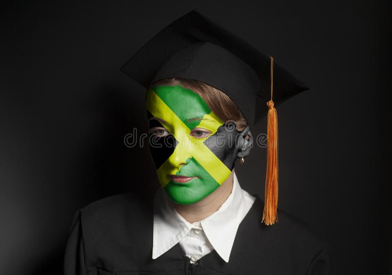 Portrait of Female Jamaica bachelor with painted Jamaica flag in Black mantle and Graduation Cap. On black stock photos