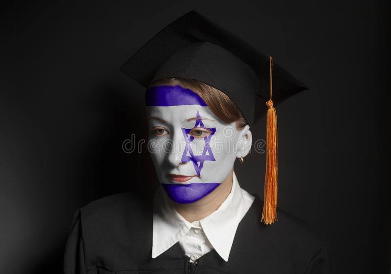 Portrait of Female Jewish bachelor with painted Flag of Israel in Black mantle and Graduation Cap. On a black background stock photos