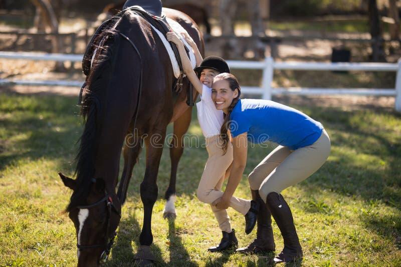 Portrait of female jockey assisting girl royalty free stock photo