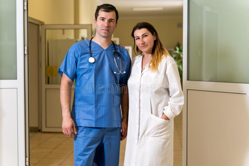 Portrait of  female and male doctors in white robe and blue scrubs on blurred hospital corridor background. Portrait of couple in middle age, Caucasian white royalty free stock image