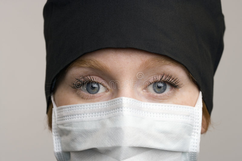 Portrait of female medical staff. Close up of female medical staff wearing surgical mask and cap royalty free stock photos
