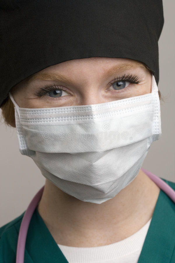 Portrait of female medical staff. Close up of smiling female medical staff wearing surgical mask stock images
