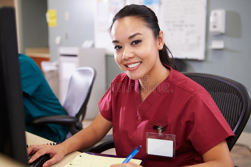 Portrait Of Female Nurse Working At Nurses Station. Holding Pen Looking To Camera Smiling stock images