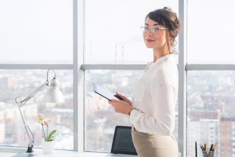 Portrait of female office manager in wearing elegant dress, using her tablet computer, standing near workplace, looking royalty free stock photo