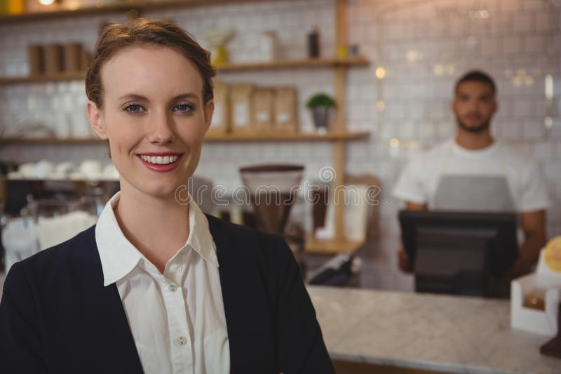 Portrait of female owner with waiter working in background royalty free stock images