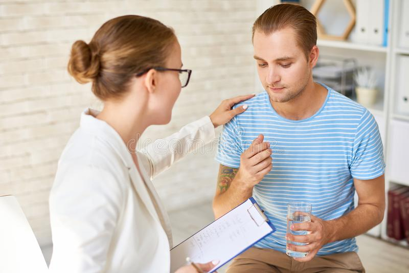 Young Man Opening Up in Support Group. Portrait of female psychiatrist comforting crying young men during group therapy session, providing counseling and support royalty free stock image