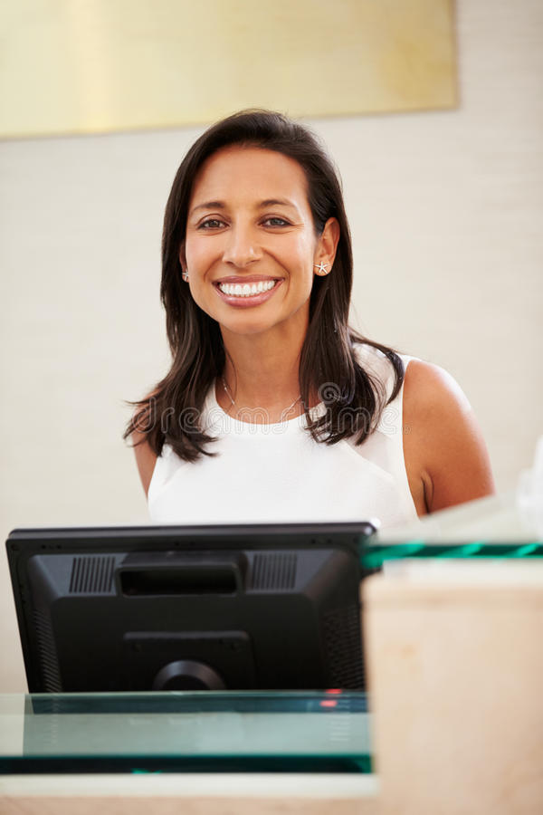 Portrait Of Female Receptionist At Hotel Front Desk stock photography