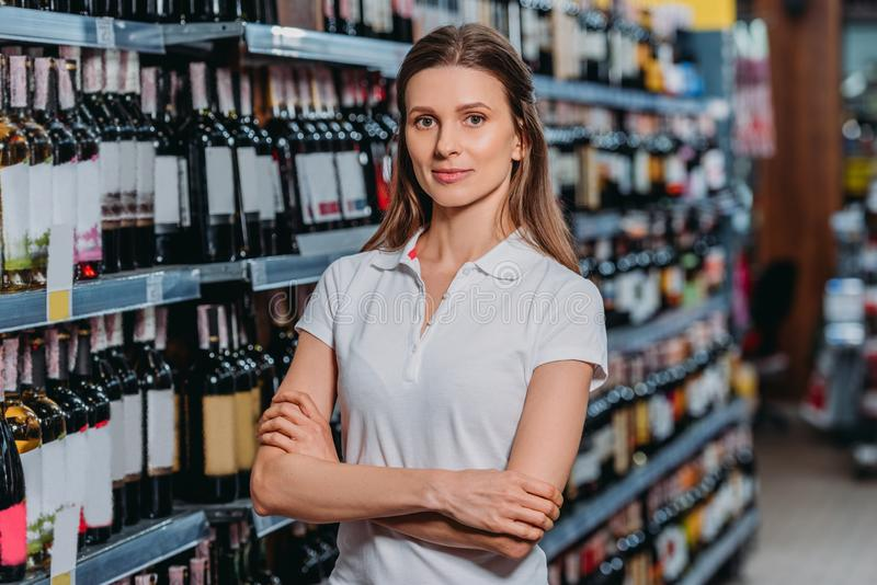 portrait of female shop assistant with arms crossed looking at camera stock photo