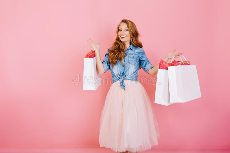 Portrait of female shopaholic holding paper bags from favorite stores and smiling,  on pink background royalty free stock photos