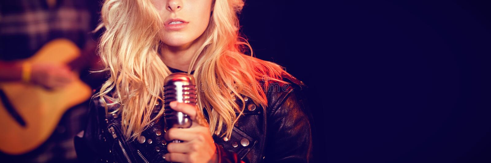 Portrait of female singer with blond hair. At concert in nightclub royalty free stock image