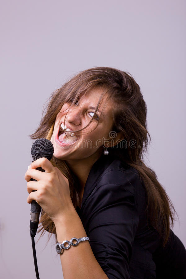 Portrait of female singer holding microphone stock photo