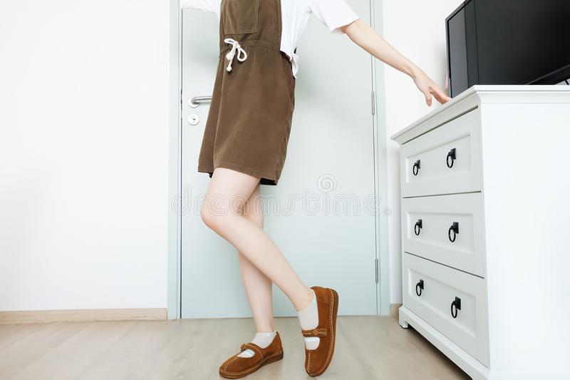 Portrait Female Slim Legs. Girl Long Leg. Beautiful Woman in Brown Dress and Brown Shoes Standing and Posing in The White Roo stock images